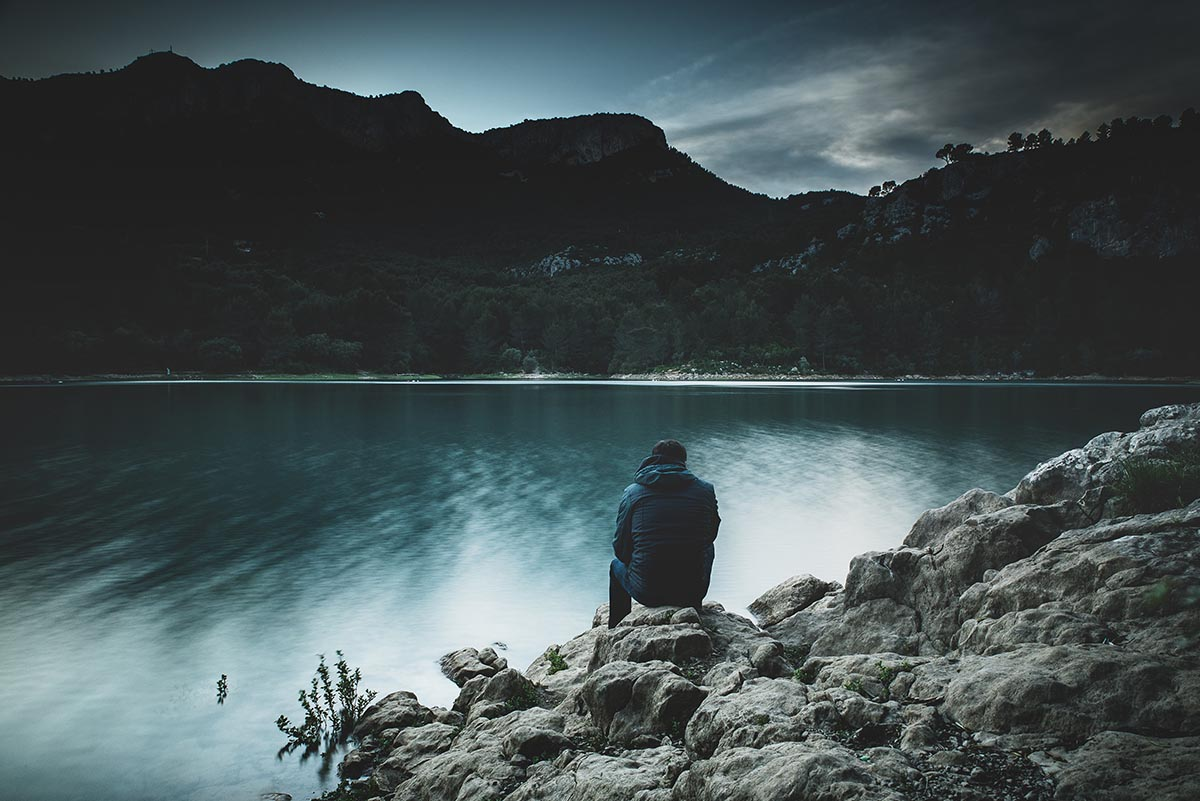 man looking over lake and mountain, similar to Abraham thinking about the Promise God made to him.