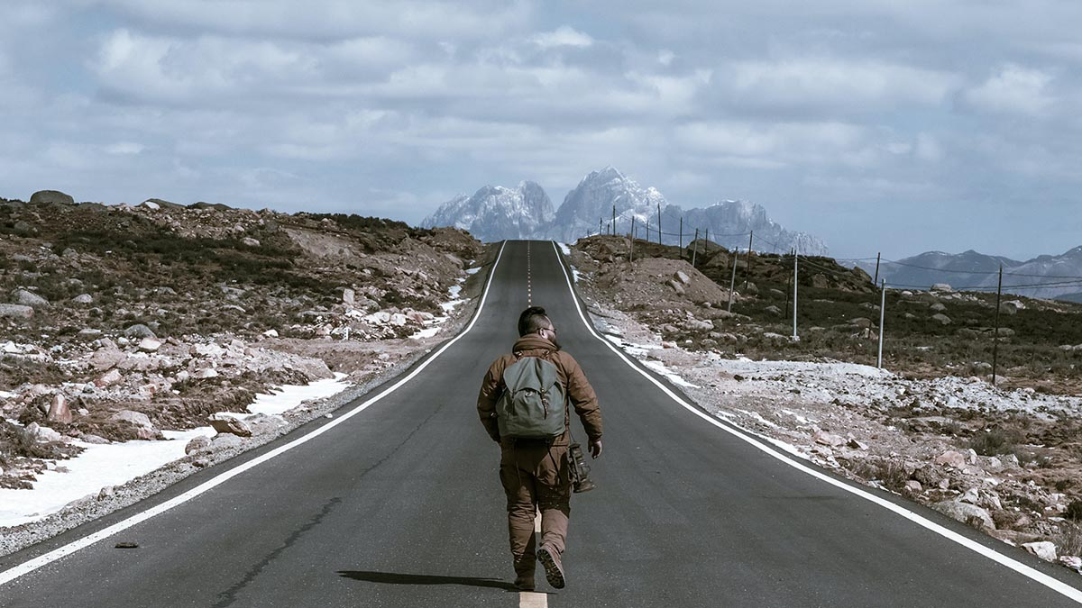 Picture of a solitary man walking down a paved road cutting between a hill with mountains at the end.