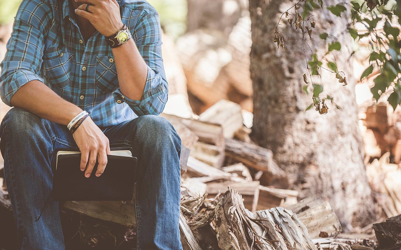Image of a man sitting on wood, reflecting on his thoughts and holding a small book..
