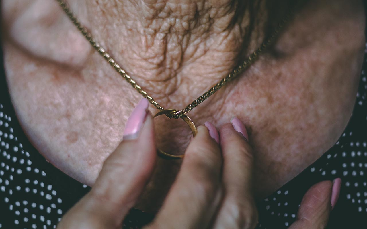 Cropped picture of an older woman's neck and she's holding a ring attached to a necklace.