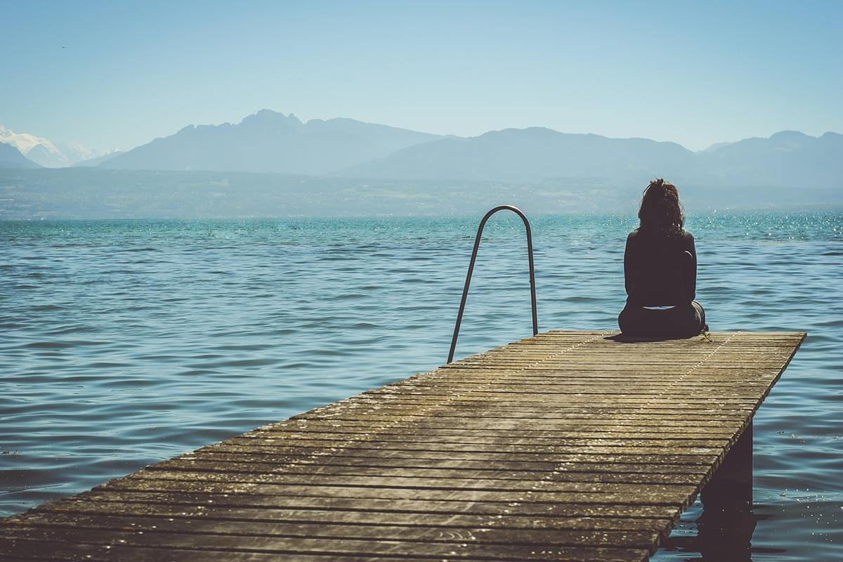 Image of a woman sitting at the end of a dock facing the water and mountains far away.